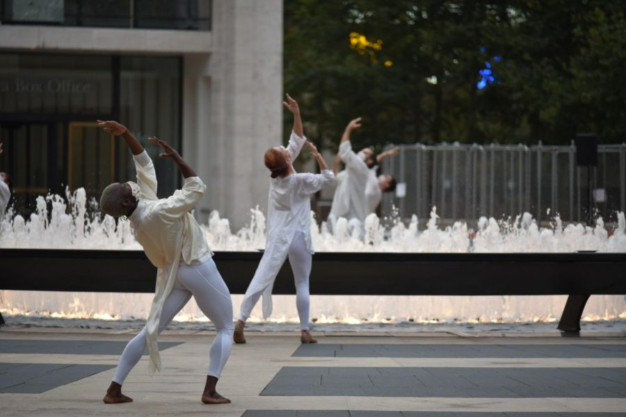 two dancers dressed in white in front of a fountain for table of silence
