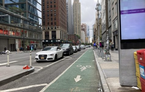 a bike lane next to the sidewalk with a barrier of parked cars separating it from the street