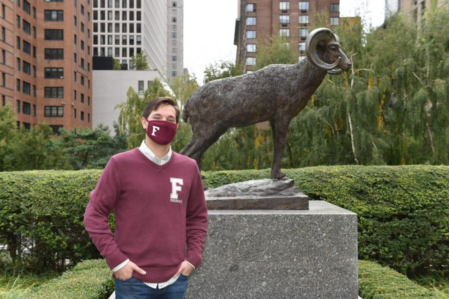 Robert Sundstrom wearing a Fordham hat and mask poses in front of the ram statue in the Outdoor Plaza