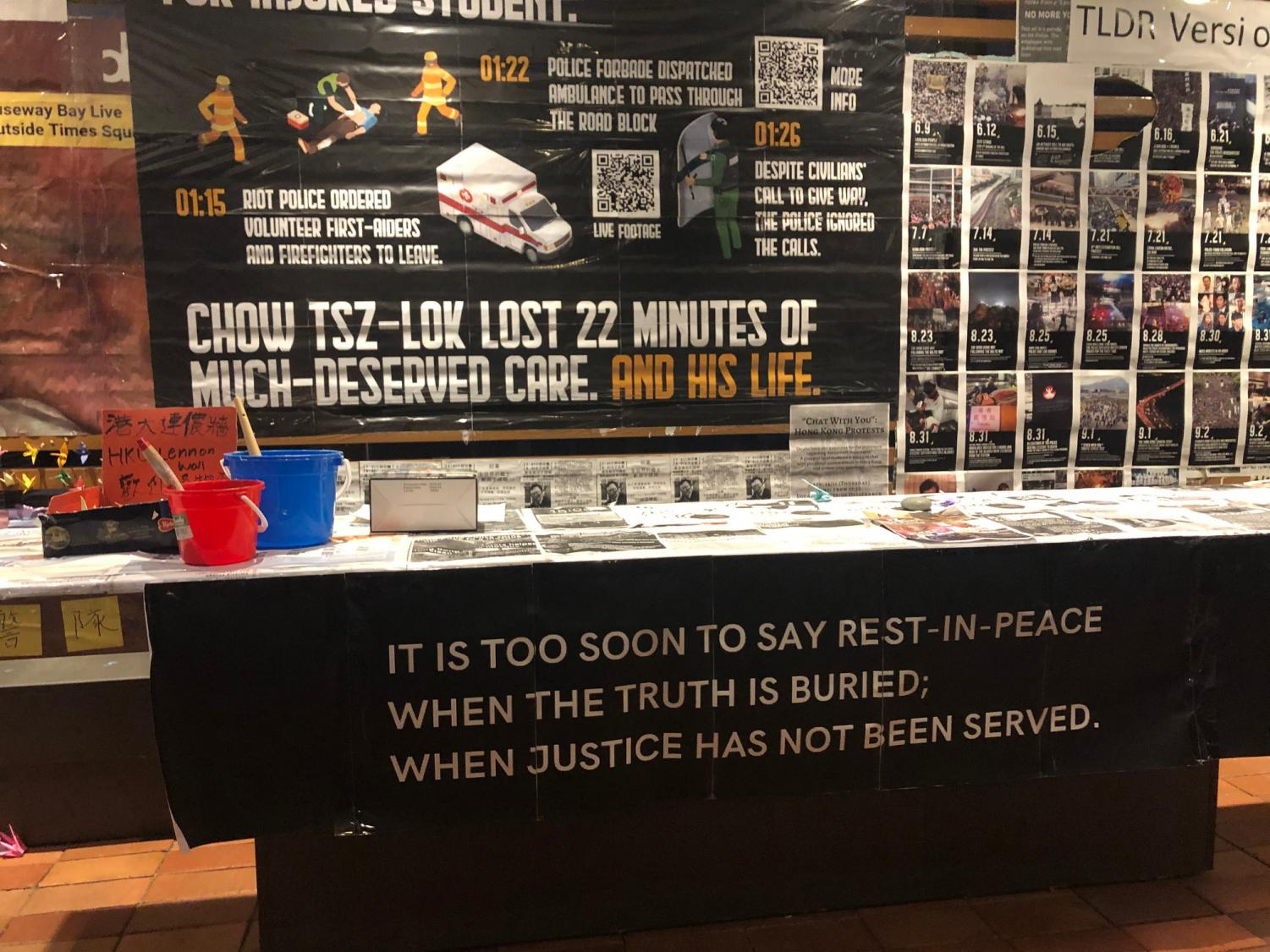 """a memorial with a banner reading """"it is too soon to say rest in peace when the truth is buried. when justice has not been served."""" above is a sign reading """"chow tsz-lok lost 22 minutes of much-deserved care. and his life."""""""