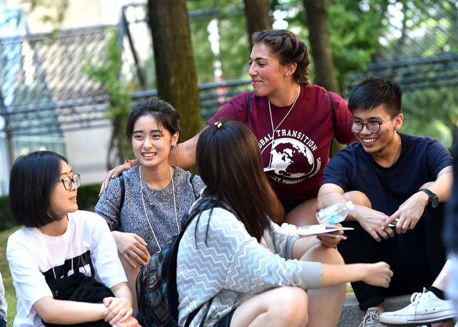a group of international students smiling as they sit in a group on the Outdoor Plaza