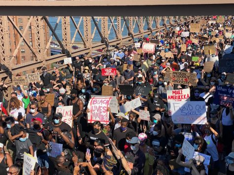 a large crowd of BLM protestors crossing a bridge while carrying signs