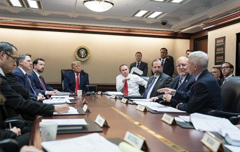 president and group of people sitting at a conference table discussing a vaccine