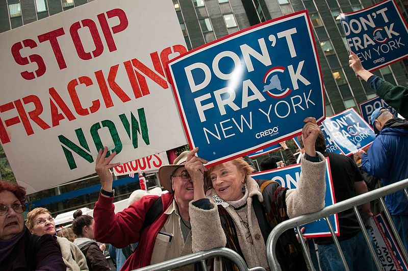 protestors holding up signs against fracking
