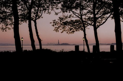 Park at sunset with Statue of Liberty standing across the water
