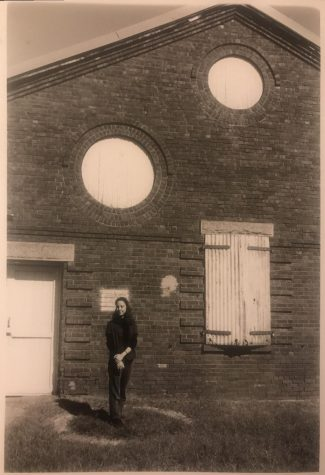 In black and white, woman stands in front of old building