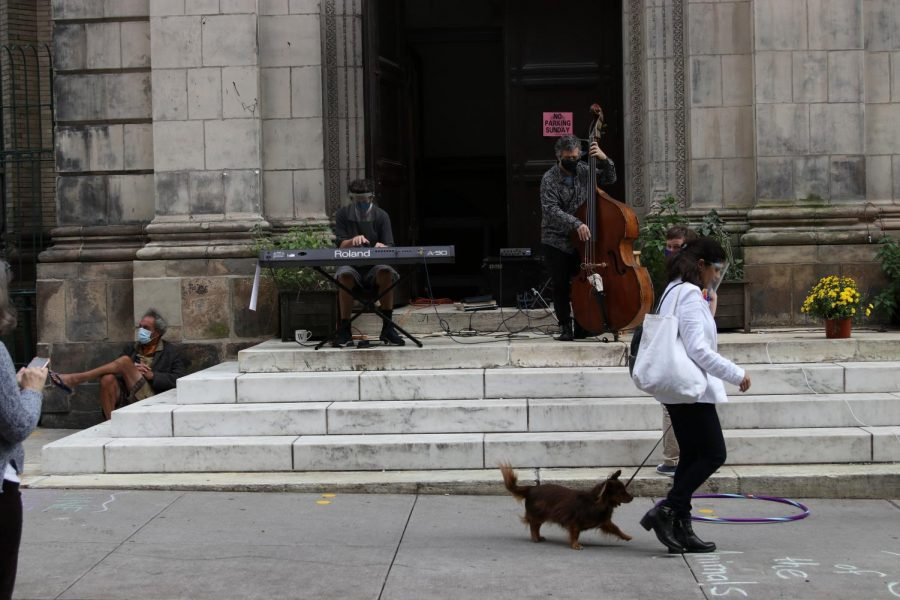 man playing upright bass at the top of a short church staircase, with a woman walking her dog in the foreground