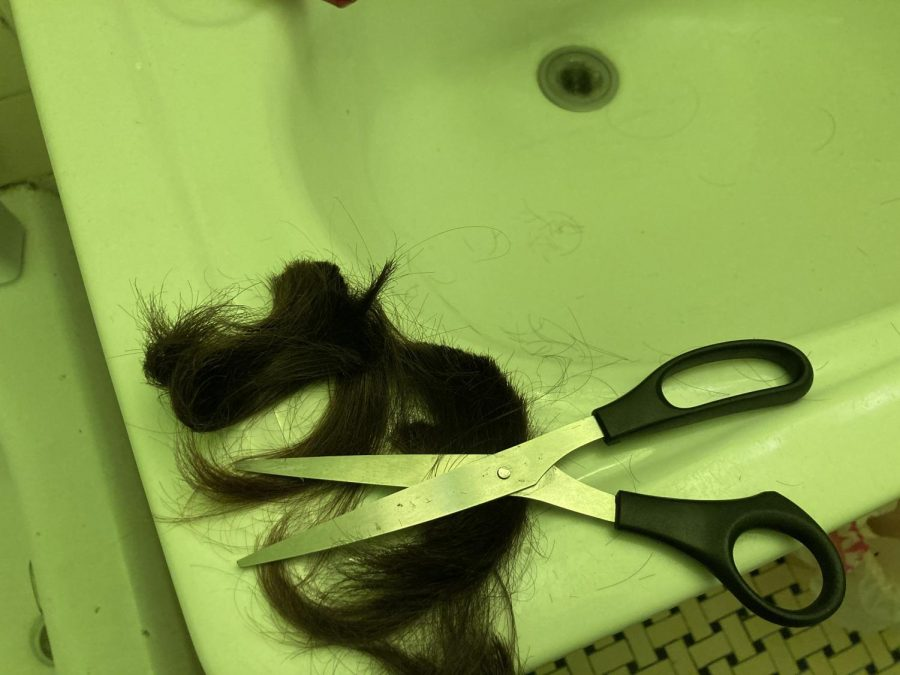 a chunk of hair next to scissors on the edge of a sink after cutting their hair into a mullet