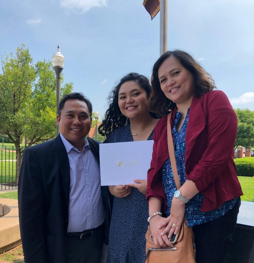 the writer holding a certificate of citizenship with her parents standing to either side of her
