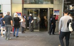 voters wait in line at a NYC polling site. Signs can be seen reading VOTE HERE in English, Spanish, and Chinese