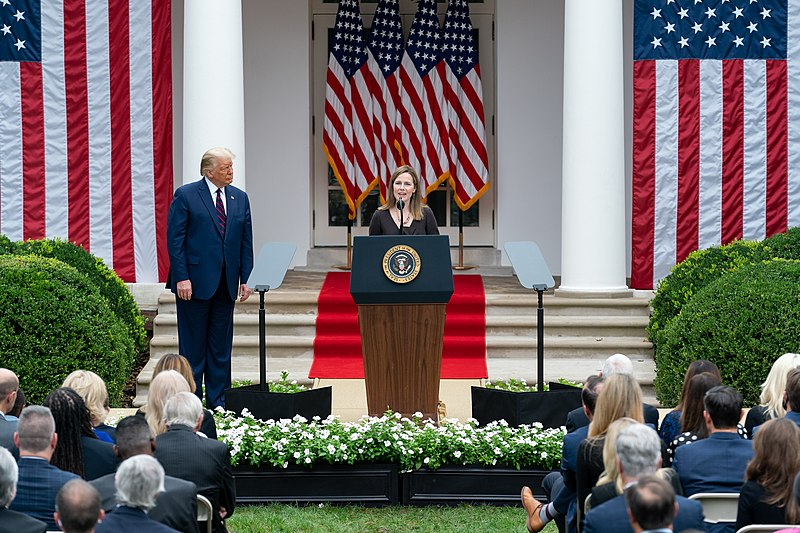 Amy Coney Barrett standing at a podium addressing a crowd on the lawn in front of the White House with American flags behind her and Donald Trump standing to her right