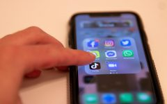 a finger holding down the tiktok app on an iphone to delete it