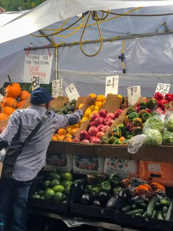 a man reaches to grab a piece of fruit from a produce stand