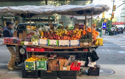 a fruit stand on the corner of midtown street in NYC