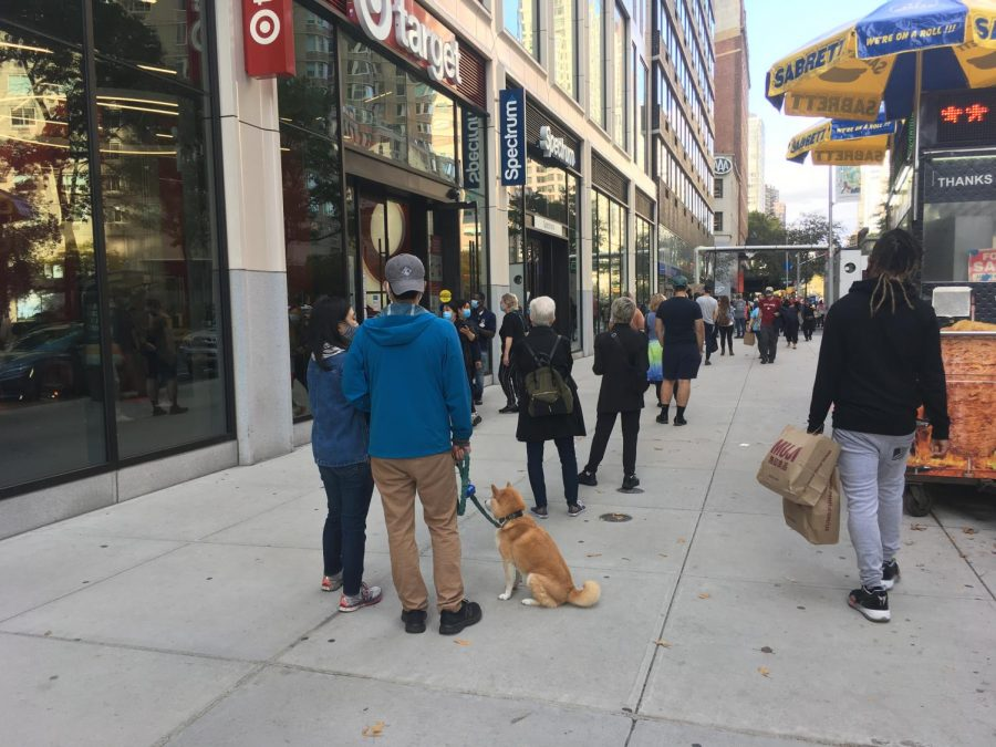 line of people standing on a sidewalk, including a dog