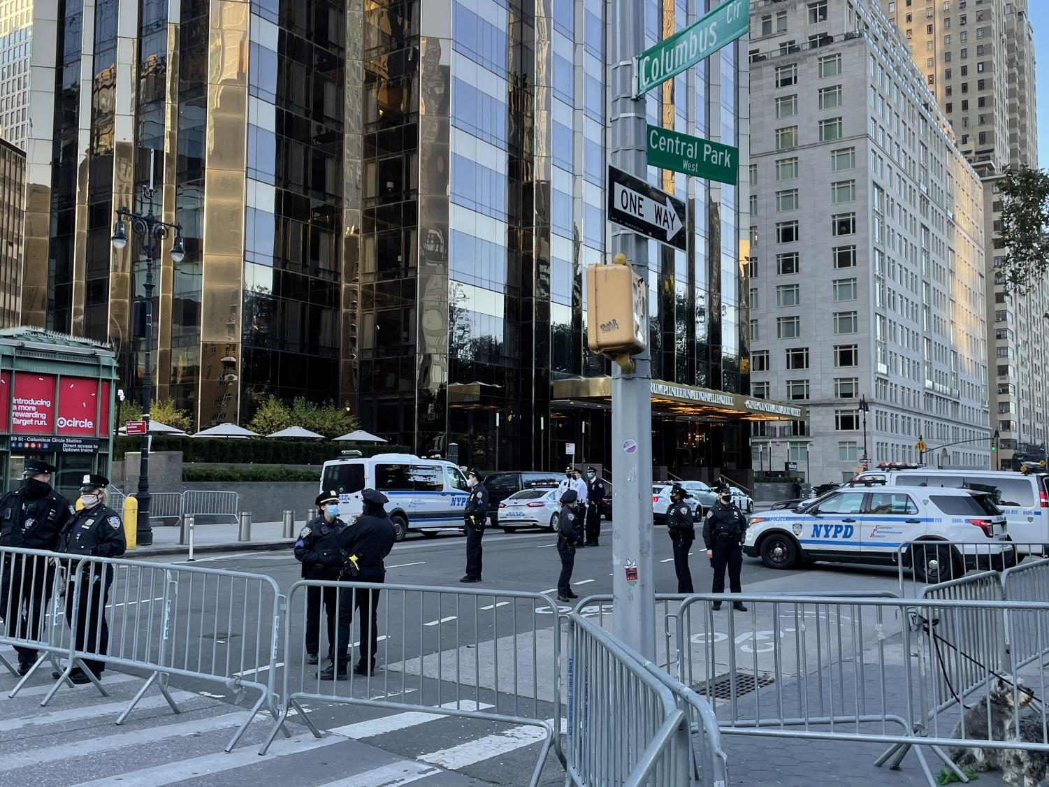 police officers stand in the street on Central Park West with a fence blocking traffic to the street and police cars lining the sides