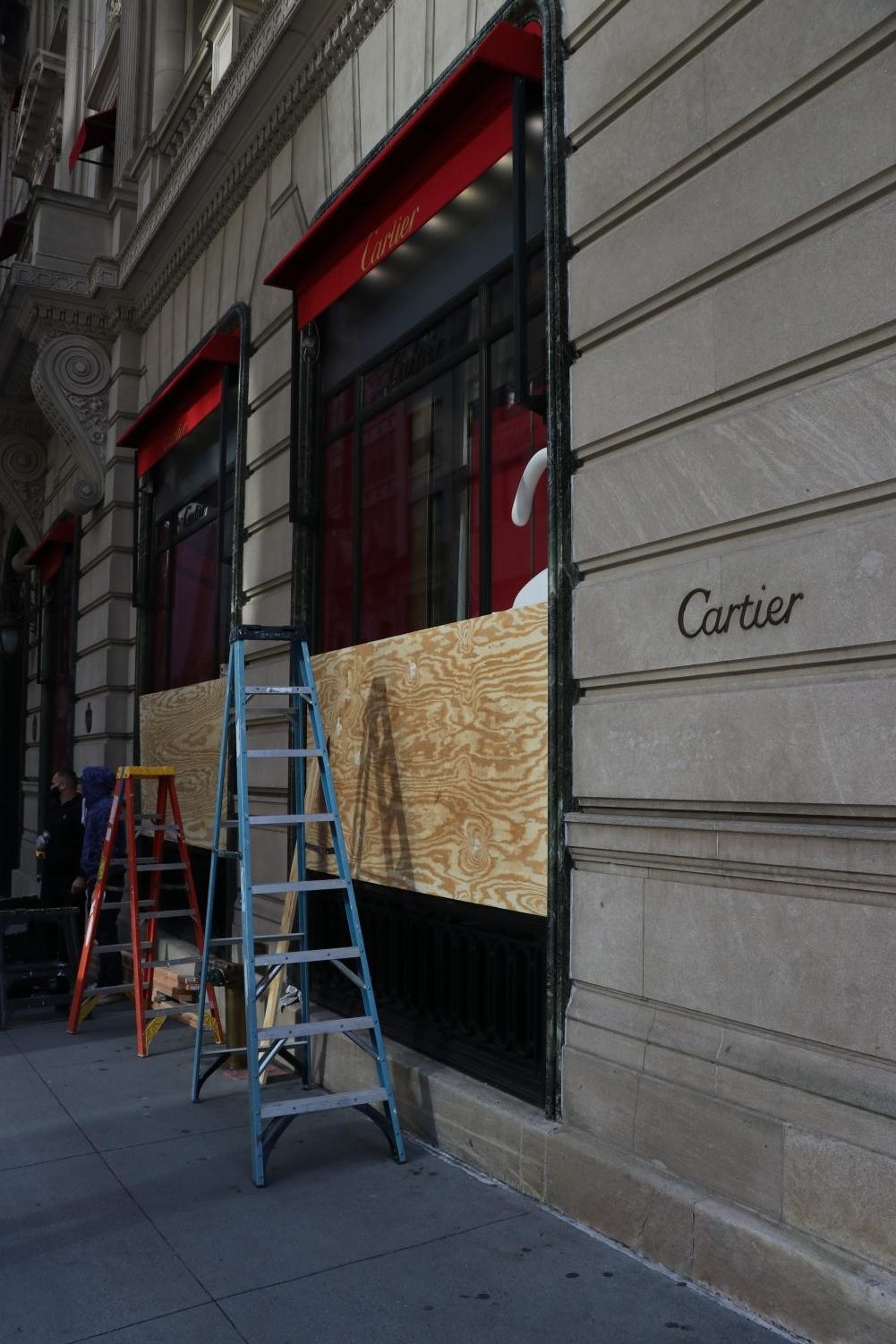 a ladder stands on the sidewalk as boards are put up on the windows of a Cartier store