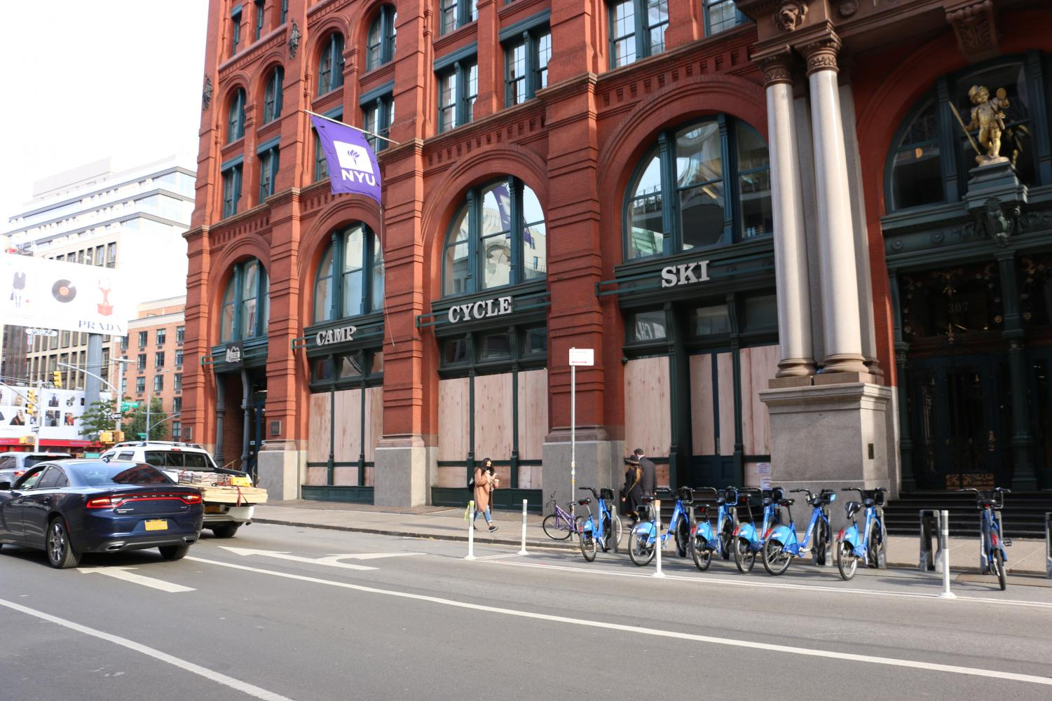 the boarded up REI store in Soho with a purple NYU flag flying above