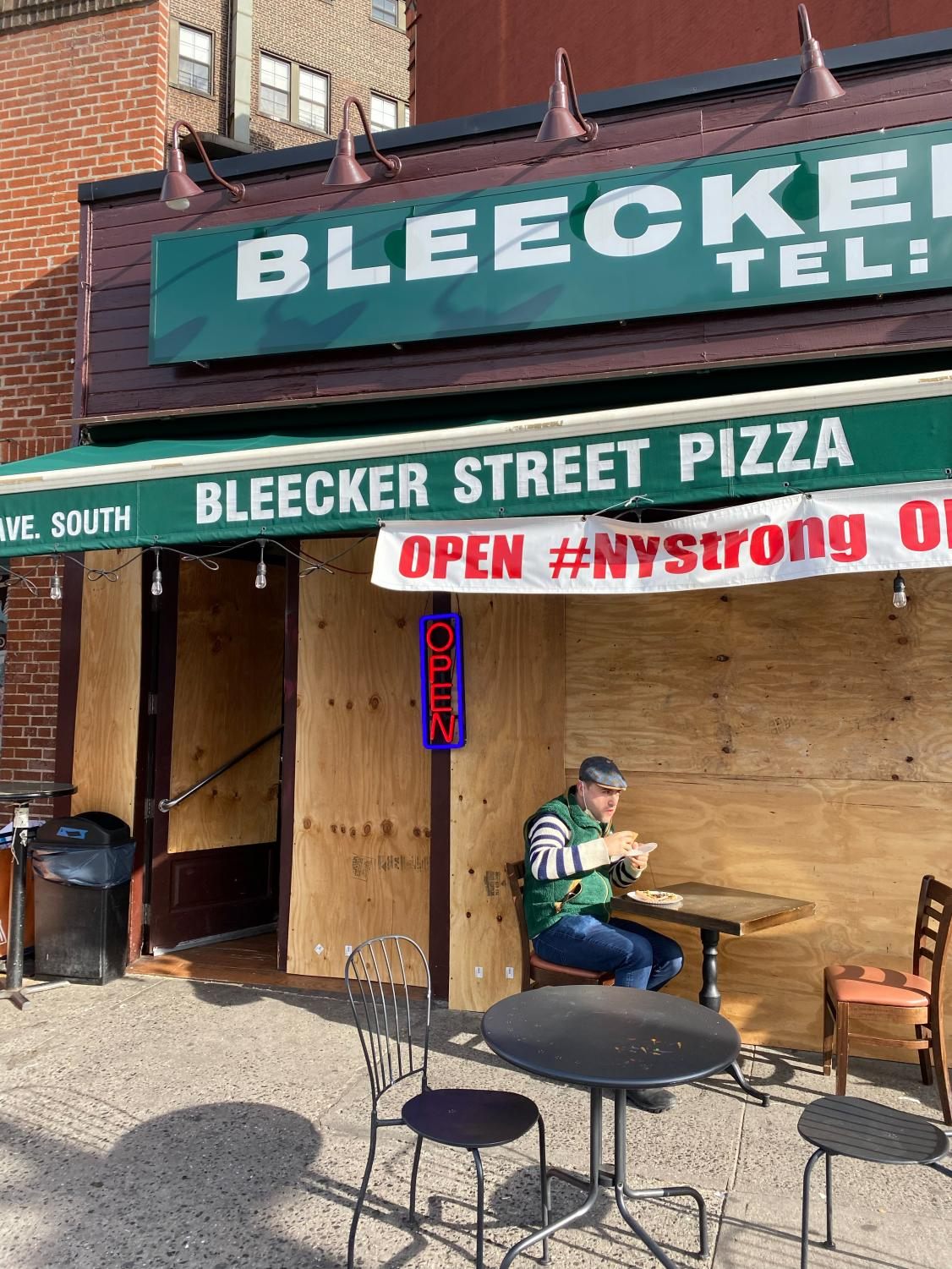 Bleecker Street Pizza with the windows boarded up and a patron eating a table outside