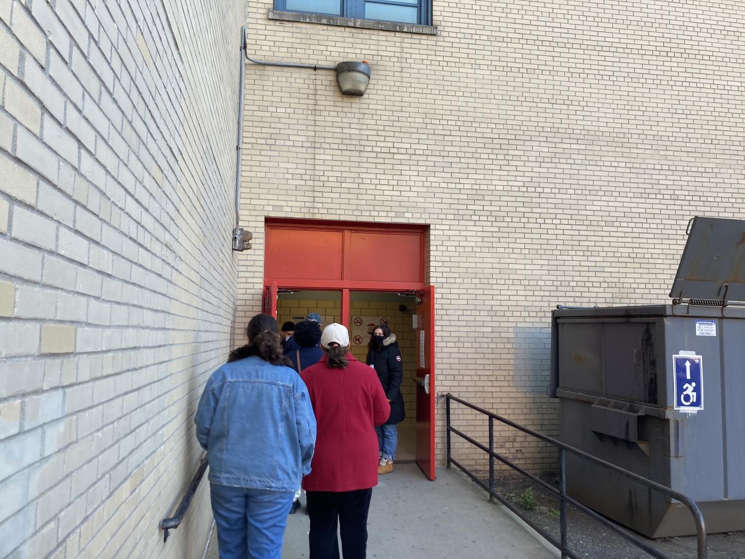 a line of voters waits outside a door