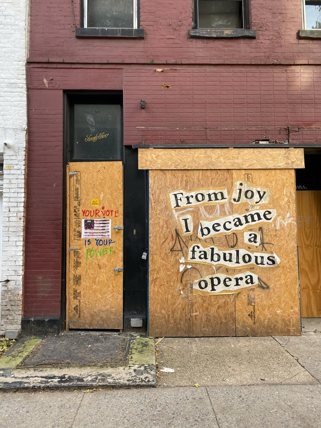 """A boarded up building with the phrase """"From joy I became a fabulous opera"""" stickered on the boards"""