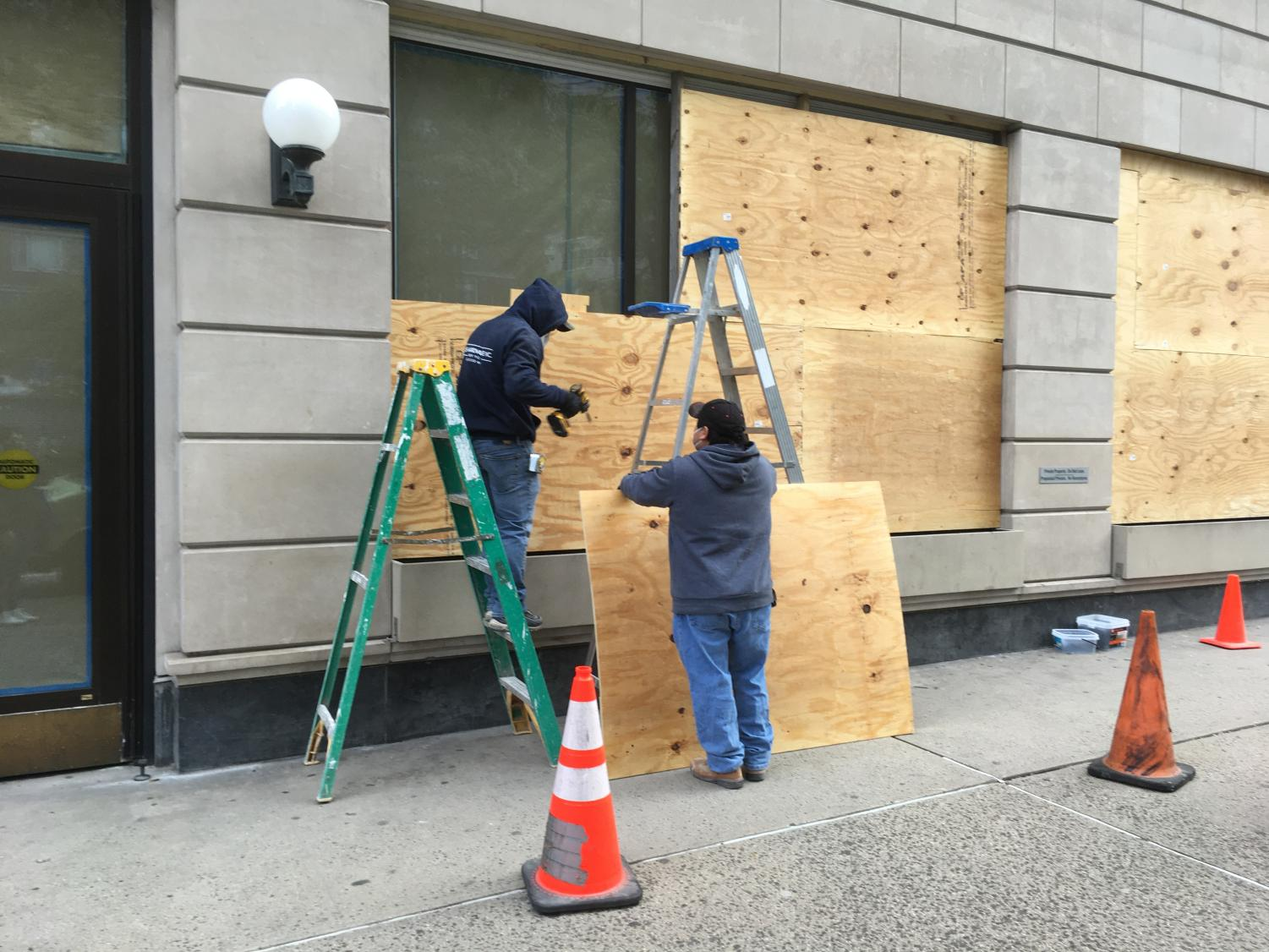 one worker holds a board while another stands on a ladder with a drill