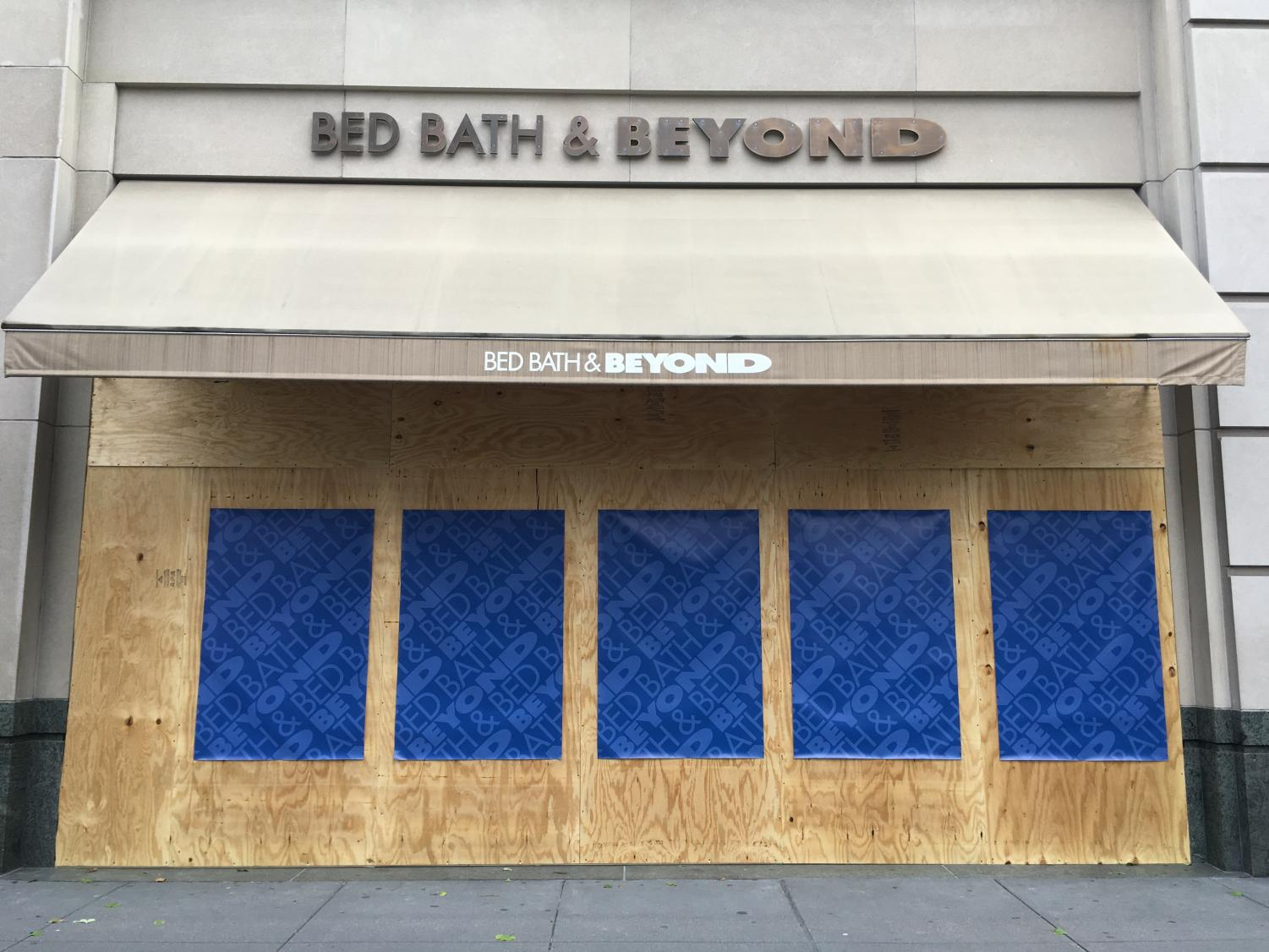 Bed, Bath, & Beyond with a boarded up storefront covered in branded posters for the store