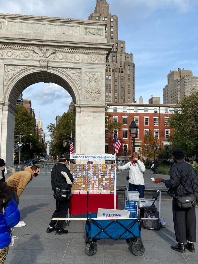 A button vendor in Washington Square Park with the Arch behind her