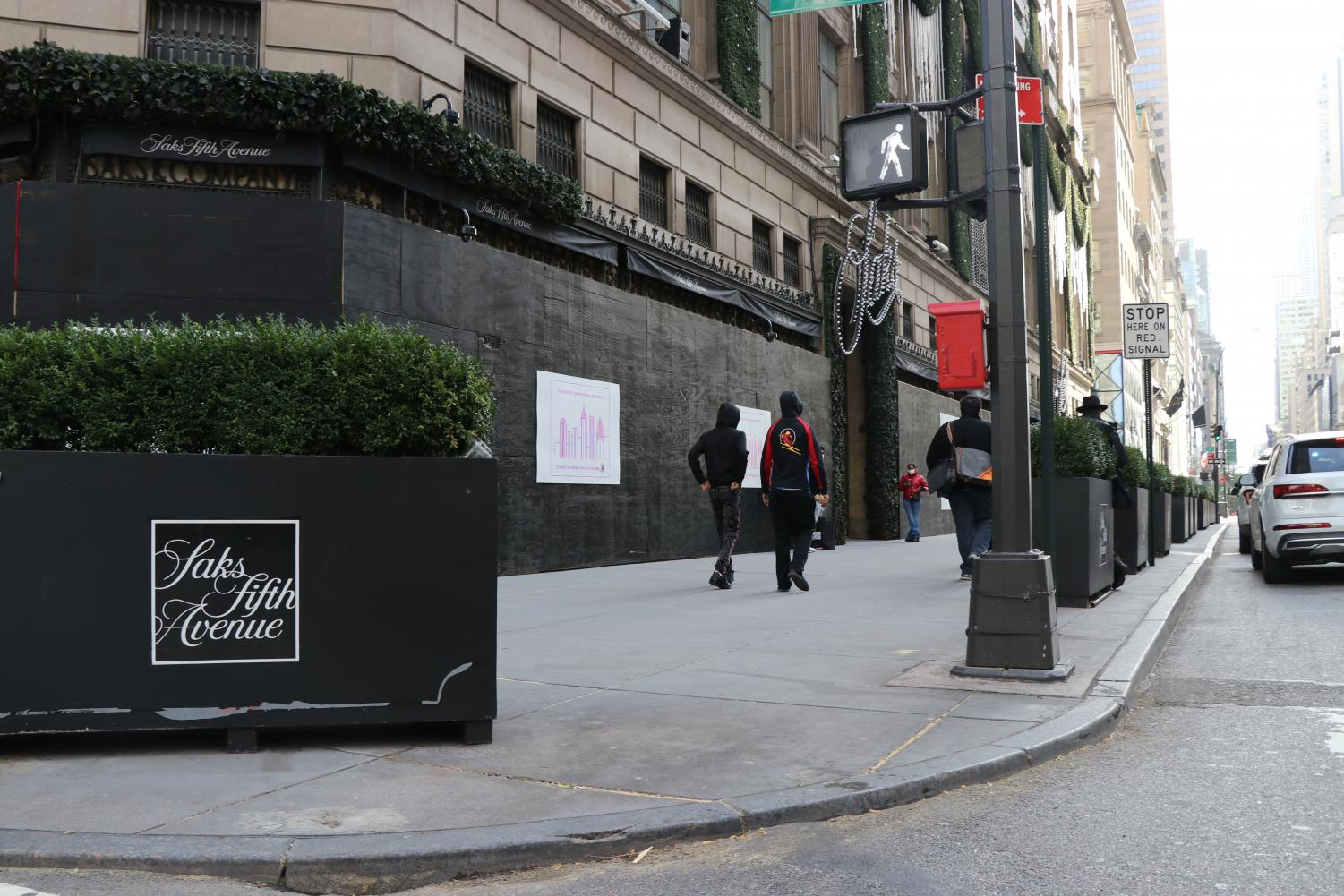 the storefront of Saks Fifth Avenue entirely covered in black boards