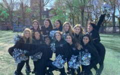 group of girls, fordham's dance team, on a football field with black uniforms and silver pom-poms