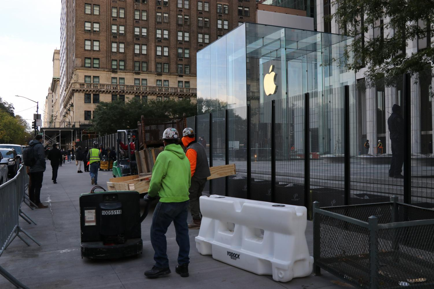 workers erect a fence in front of the Apple store