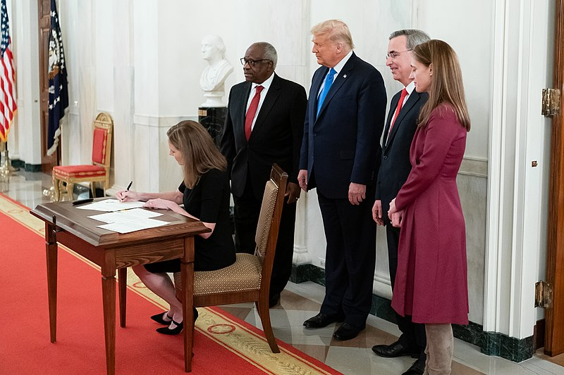 Amy Coney Barrett signs a document while President Trump, Clarence Thomas, and two others stand behind her