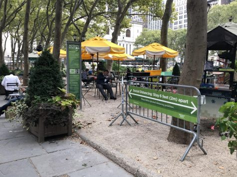 sign reminding people to social distance while in bryant park's spaces