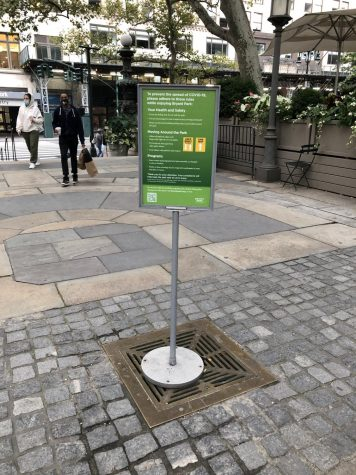 sign with social distancing reminders in one of bryant park's stone spaces