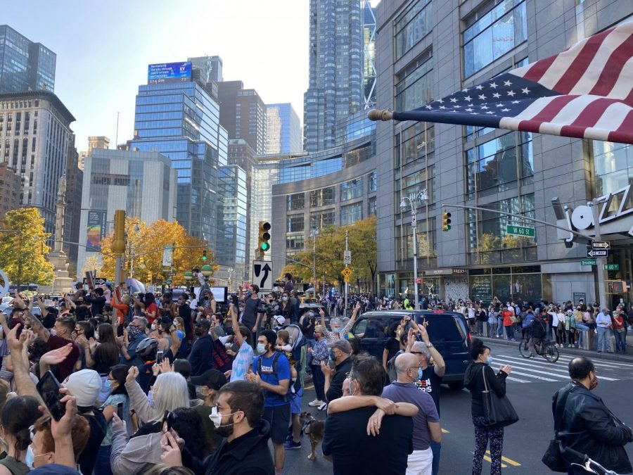 people celebrate the victory of Biden the street on Broadway in front of Trump International Hotel