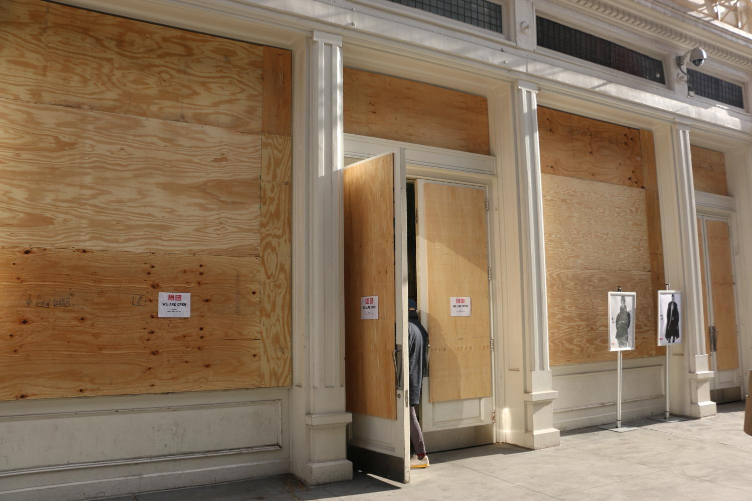 the UNIQLO store with boards on the windows and doors but with the door open for customers to come in