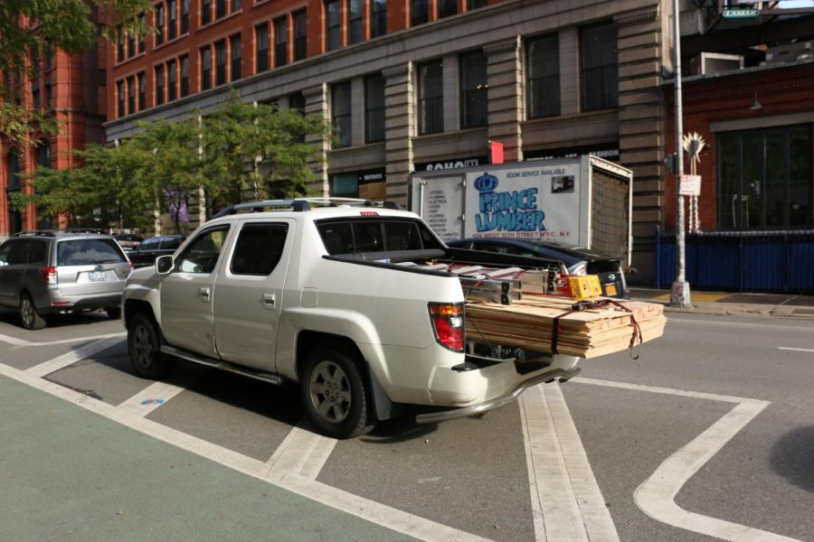 a pickup truck with the back filled with boards and ladders parked on the street