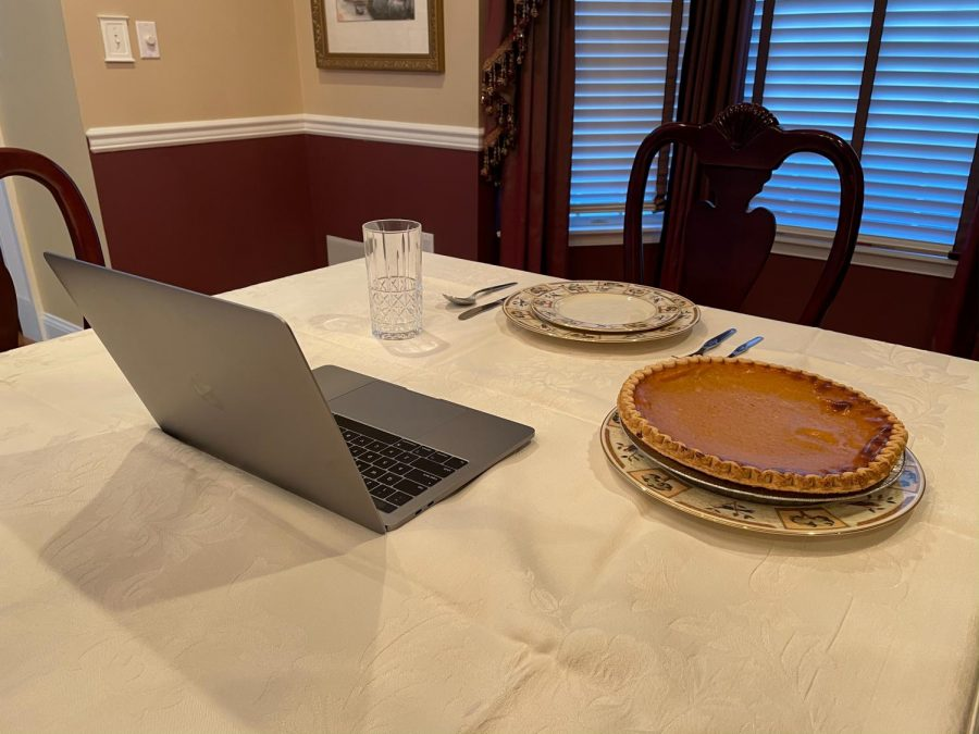 a laptop and pumpkin pie sit on a set dinner table
