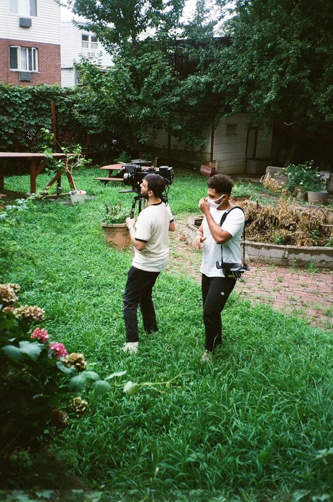 Enrique holds a camera while Tommy fulfills his role as director