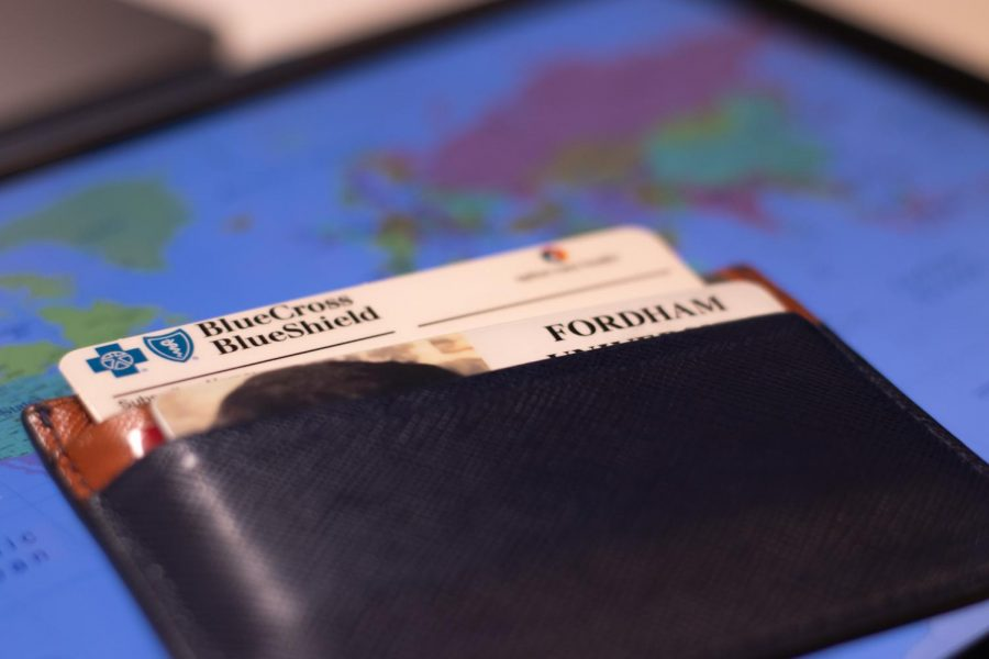 a wallet with a Fordham ID card in the front and a health insurance card sticking out behind it