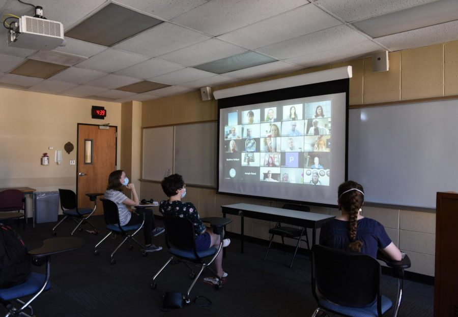 students in a classroom watching a hybrid class on zoom. spring 2021 registration will include online and hybrid classes.