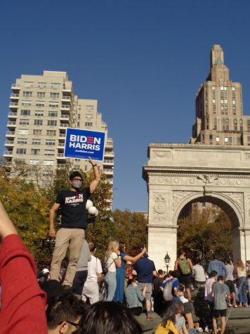 someone holds a Biden Harris sign in front of the Washington Square Arch