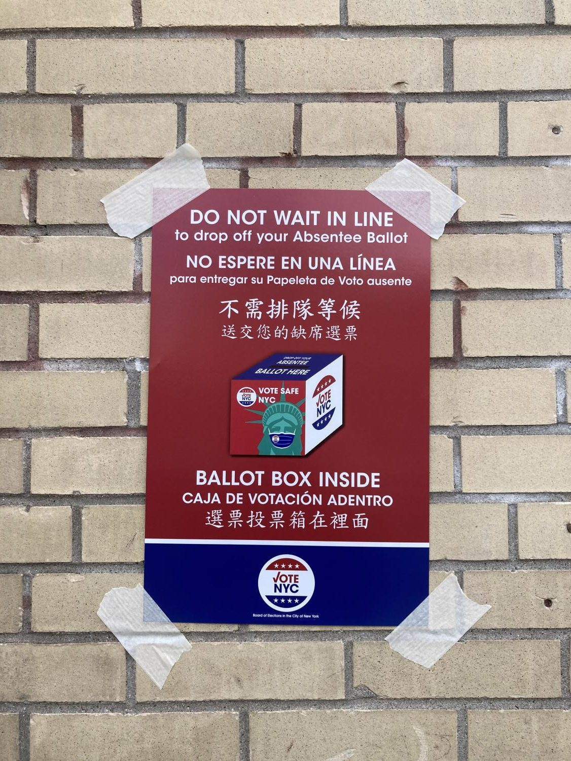 """a sign that reads """"do not wait in line to drop off your absentee ballot. Ballot box inside"""""""