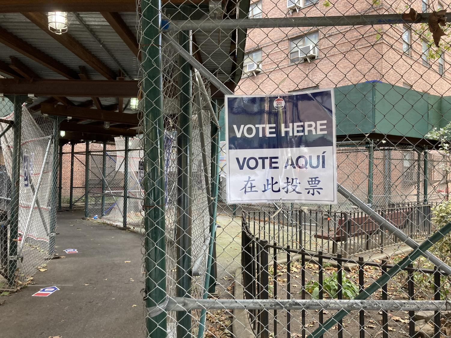 """a sign on chain-link fence that reads """"Vote Here"""""""