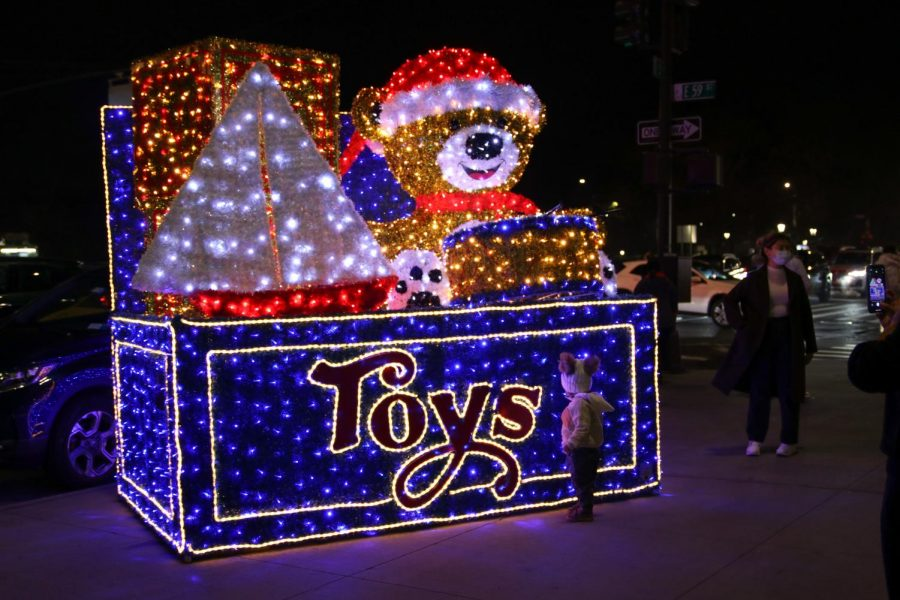 A giant box of toys on the sidewalk of Fifth Avenue, which is part of a collection of similar light-up decorations lining the street.