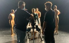 the two filmmakers stand on either side of the camera talking while the cast is in the background