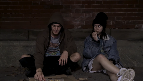 two actors sitting against a brick wall eating french fries as part of the show nineveh for the studio fest