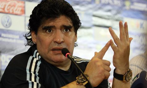 maradona with his hand up, pointing to one of his fingers