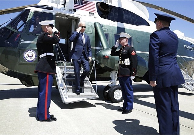 Biden steps off of Marine One while saluting the soldiers