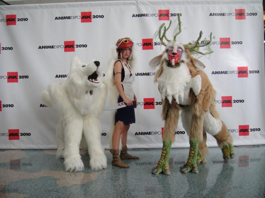 three anime fans pose in costumes at a convention